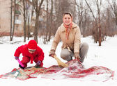 Woman with child cleans rug with snow — Stock Photo