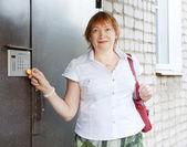 Woman uses intercom in door — Stock Photo