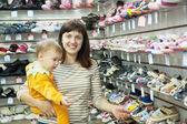 Szczęśliwa matka z dzieckiem wybiera buty — Zdjęcie stockowe