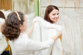 Woman with bride chooses white fur cape at store — Stock Photo