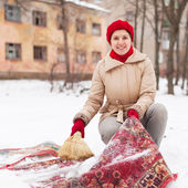 Girl in red cap cleans carpet with snow — Stock Photo