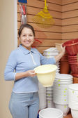 Woman chooses plastic flower pot — Stock Photo