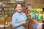 Mature woman chooses fertilizers at store — Stock Photo
