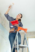 Woman paints ceiling — Stock fotografie
