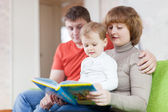 Parents with child looks the book — Stock Photo