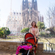 Woman with stroller in front of Sagrada Familia — Stock Photo
