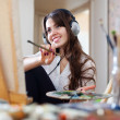 Long-haired artist in headphones paints picture — Stock Photo #25914689
