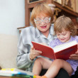 Mature woman and baby girl reads book — Stock Photo
