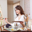 Woman paints landscape on canvas — Stock Photo