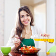 Woman pouring vegetable oil salad — Stock Photo #25916011
