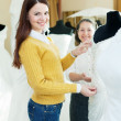 Happy women chooses bridal gown — Stock Photo