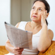 Stock Photo: Serious and wistful womwith newspaper