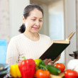 Woman reads cookbook for recipe in kitchen — Stock fotografie