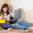 Woman with toddler   using laptops — Stock Photo