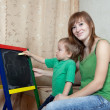 Mother and child draws on blackboard — Stock Photo