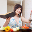 Stock Photo: Housewife cooking with cookery book