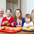Happy family drinks tea and eats cakes — Stock Photo #25917075