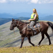 Stock Photo: Rider with backpack on horseback