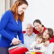 Woman pours tea from teapot for family — Stock Photo