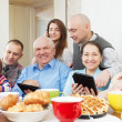 Happy multigeneration family uses electronic devices — Stockfoto