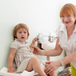 Pediatrician weighs the baby — Stockfoto