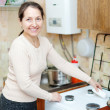 mature housewife cleans the gas-stove   — Stock Photo