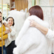 Female shop consultant helps girl chooses fur cape at shop   — Stock Photo