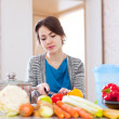 Stock Photo: Young womcooking veggie food