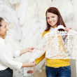 Stock Photo: Bride chooses bridal clothes at shop of wedding fashion
