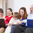 Family uses   electronic devices together — Stock Photo