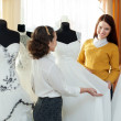 Stock Photo: Saleswomhelps girl chooses bridal outfit