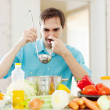 Stock Photo: Mwith ladle testing foul food