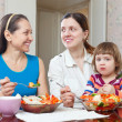 Stock Photo: Women with baby girl eats vegetables salad