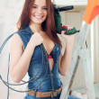 Stock Photo: Sexy girl in dungarees with drill and cable