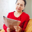 Stock Photo: Wistful womreading newspaper
