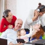 Happy multigeneration family uses electronic devices — Stock Photo #25918815
