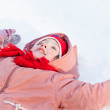Baby girl lying down on the snow — Stock Photo