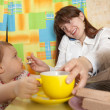 Stock Photo: Businesswoman feeding baby and speak by mobile