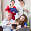 Happy multigeneration family uses few various electronic devices — Stock Photo