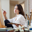 Woman paints picture on canvas — Stock Photo