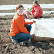 family warms the soil with polyethylene  — Stock Photo