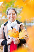 Mature woman in autumn with maple leaves — Stock Photo