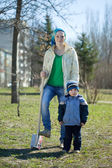 Woman and boy with spade in park — Stock Photo