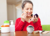 Happy mature woman in red puts facepowder — Stock Photo