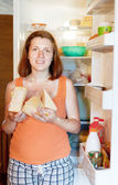 Woman with cheese near fridge — Stock fotografie