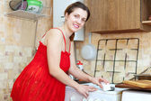 Dona de casa em vermelho o fogão com esponja de limpeza — Foto Stock