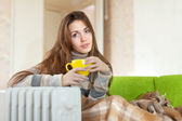 Woman with yellow cup near oil heater — Stock Photo