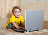 Toddler sits with laptop — Stock Photo