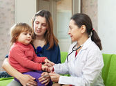 Mature children's doctor examining child — Stockfoto