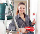 Happy woman paints wall with roller — Stock Photo